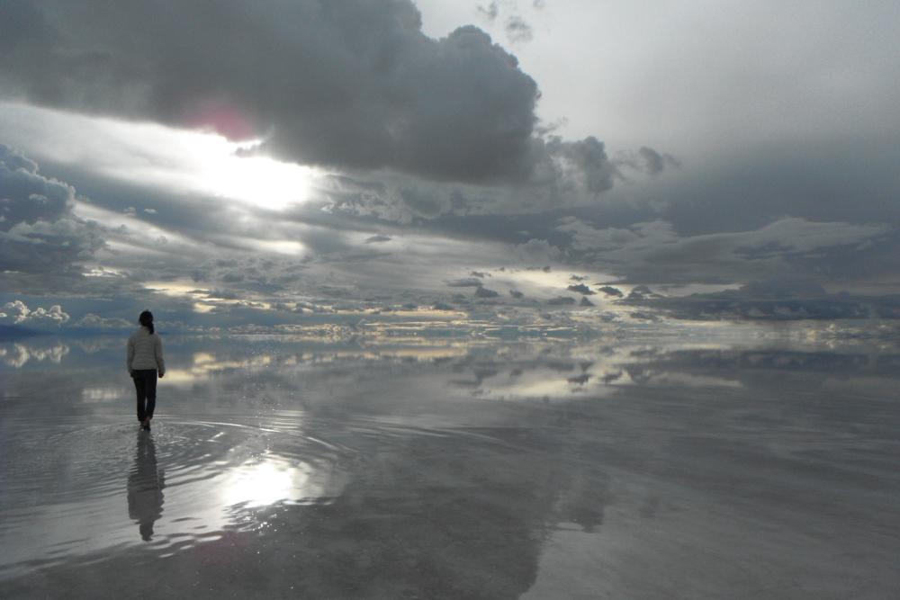 鏡張りのウユニ塩湖を歩く友達の写真