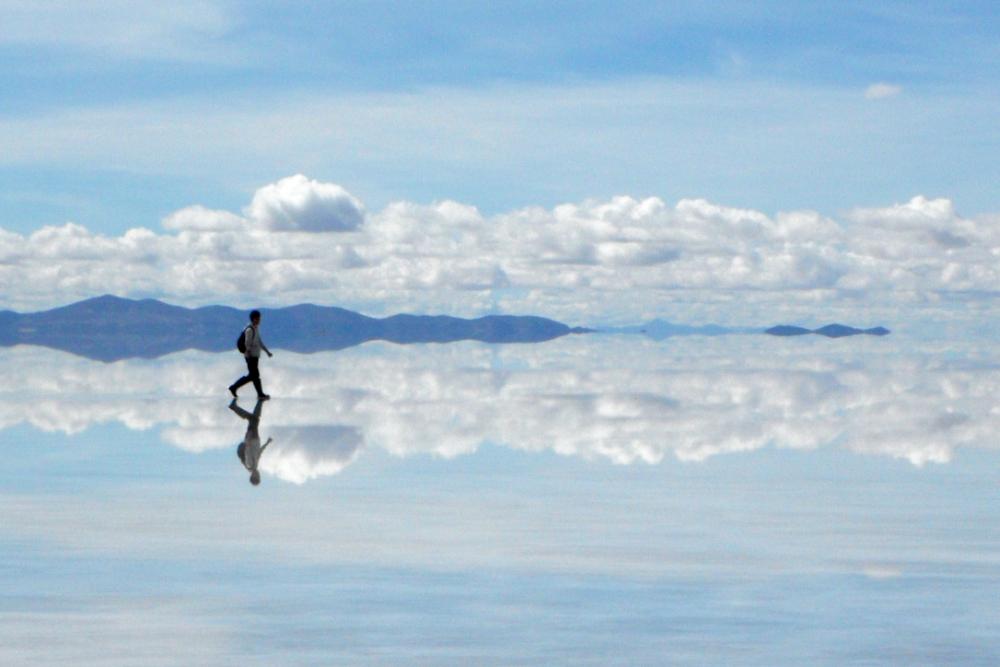 鏡張りのウユニ塩湖を歩く人の写真