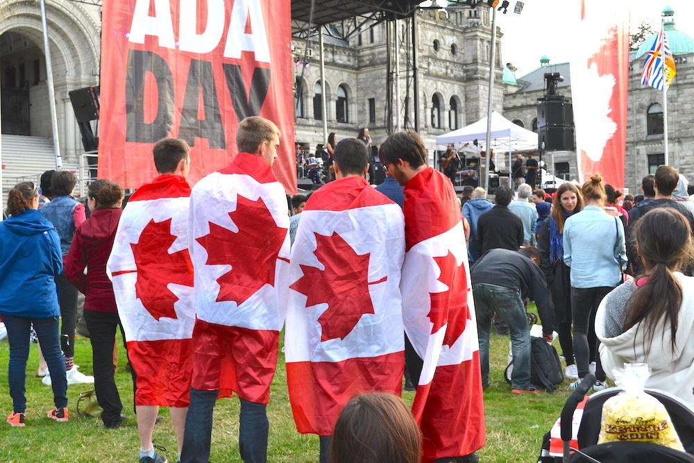 カナダ国旗を羽織る青年たちの写真