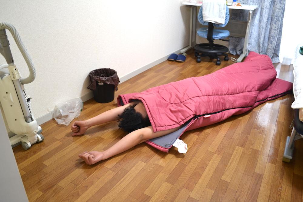 泥酔した友達(寝袋でバンザイ)の写真