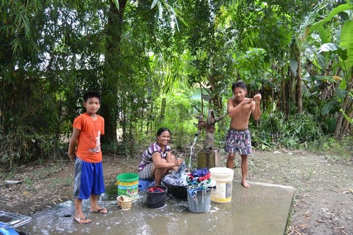 井戸水をくみ上げて洗濯している写真