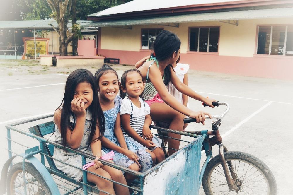 自転車で遊ぶフィリピンの子供たちの笑顔の写真