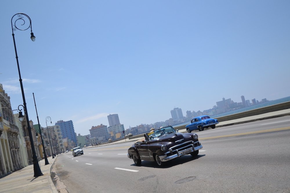 キューバ・ハバナの海沿いを走るクラシックカーの写真