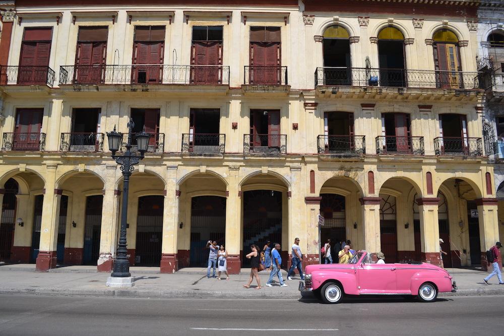 キューバ・ハバナのクラシックカー(ピンク)と建築の写真