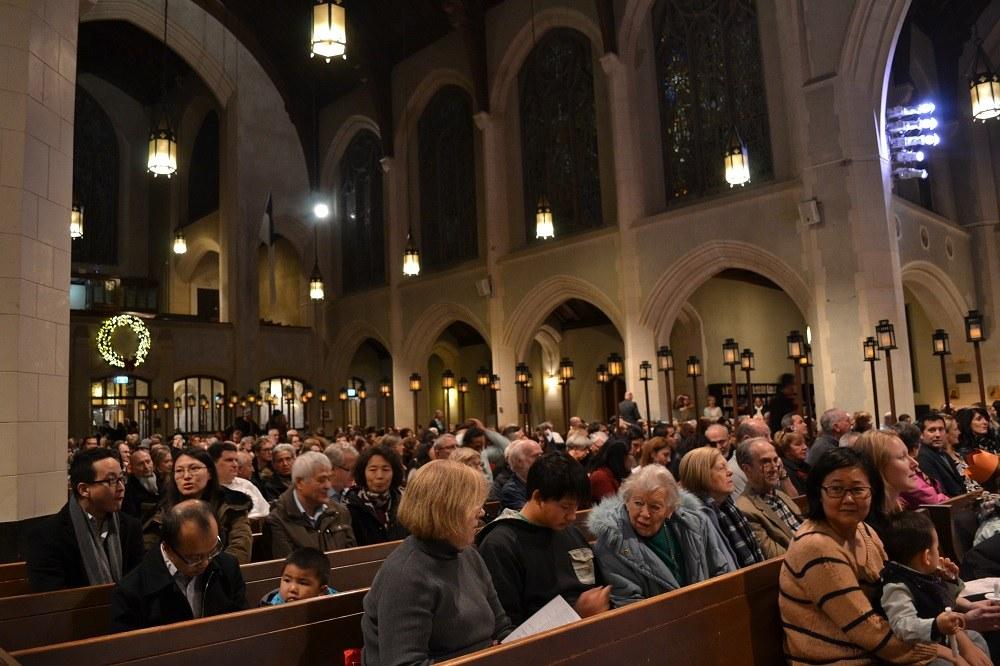クリスマスイブに教会に集まる人々の写真