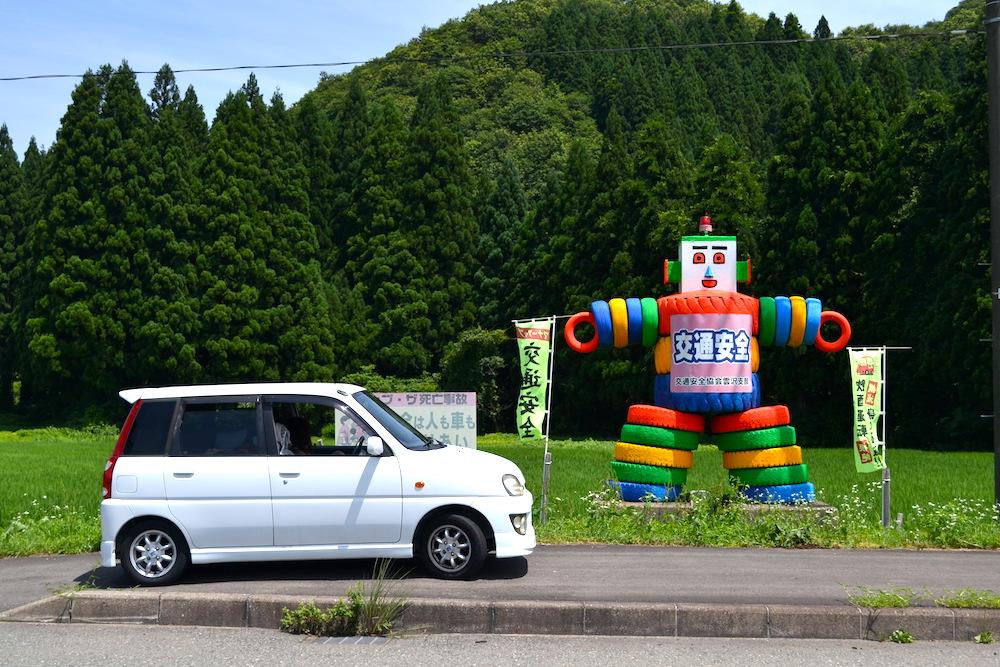軽自動車と交通安全タイヤ人形の写真