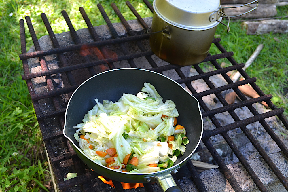 キャンプ場で薪火を使って調理の写真