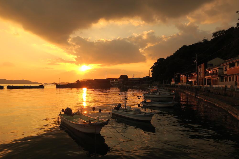 八幡浜市真穴の海沿い(ボートと夕日)の写真